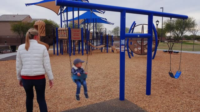 Young Mother Pushes Son on Swing Set video