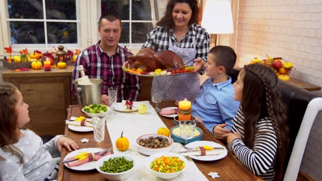 Young mother serving freshly baked stuffed turkey for Thanksgiving day