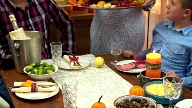vídeos y material grabado en eventos de stock de madre joven sirviendo pavo relleno recién horneado para el día de acción de gracias - thanksgiving turkey