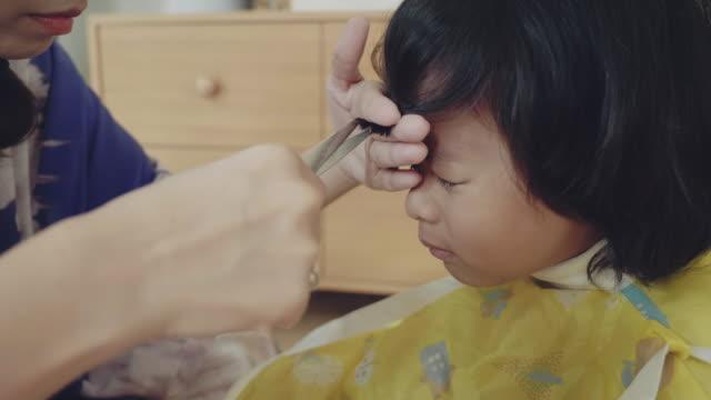 vidéos et rushes de jeune mère coiffant ses cheveux de fils à la maison. - salons et coiffeurs