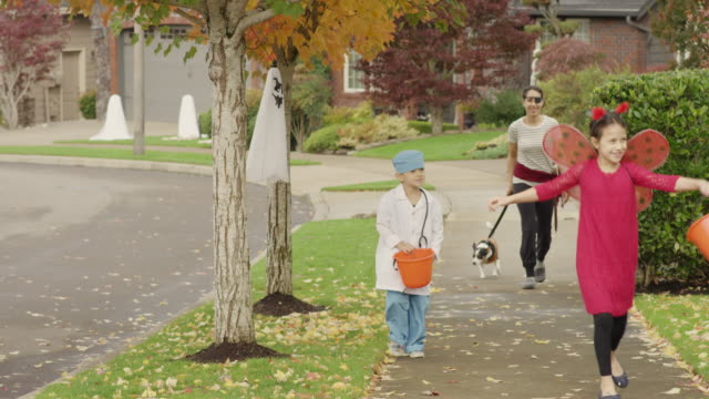 Young mother taking her children trick or treating on halloween video