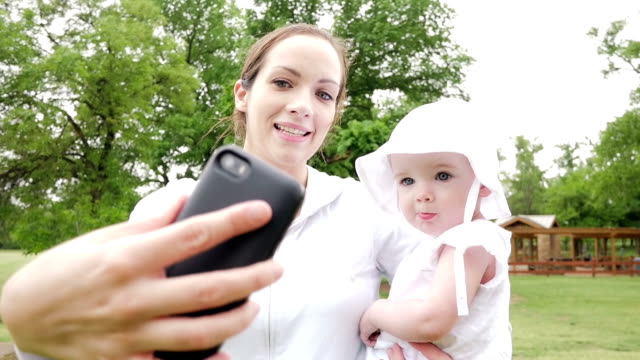 Young mother taking selfie on cell phone with toddler daughter at park video