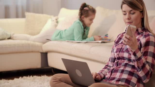 Jeune maman à l'aide d'ordinateur portable et répondre à un appel téléphonique sur portable. - Vidéo
