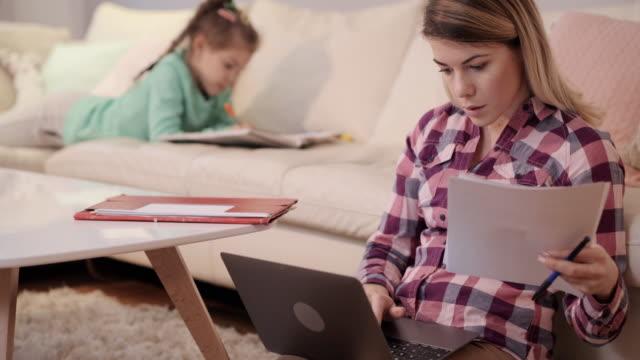 Jeune maman à l'aide d'ordinateur portable et prendre des notes tout en travaillant à la maison. - Vidéo