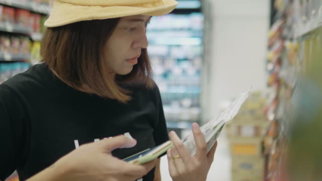 young mother using smartphone in supermarket with her boy. - paragone video stock e b–roll