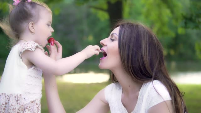 A young mother with a little daughter are feeding each other a strawberry in the park video