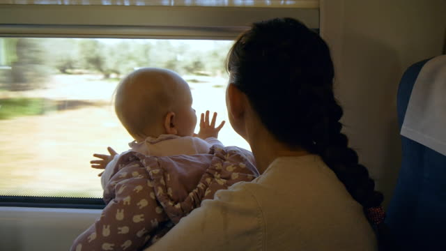 Young mother with baby in her arms traveling by train video