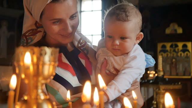 vidéos et rushes de jeune maman avec bébé observe les bougies brûlants dans l'église en slow motion - baptême