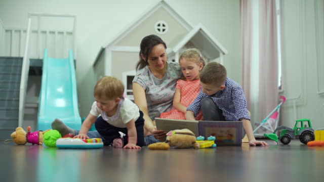 Young Mother with Children Reading a Book Young Mother Reading a Book with Children While Sitting on the Carpet in Messy Room. Concept of Childhood and Educational Games cousin stock videos & royalty-free footage