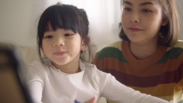 młoda matka z córką odrabia pracę domową na cyfrowym tablecie w domu. - praca domowa filmów i materiałów b-roll