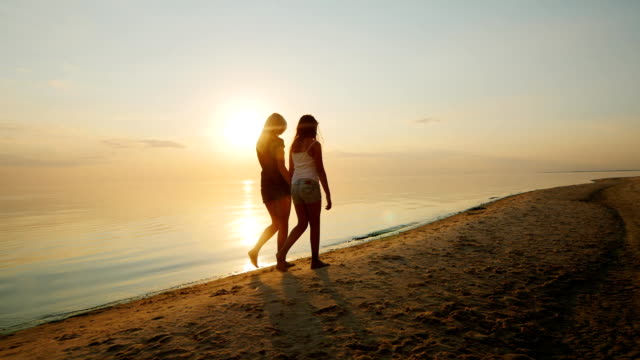 Young mother with her daughter, a teenager walking on the beach at sunset. Back view video