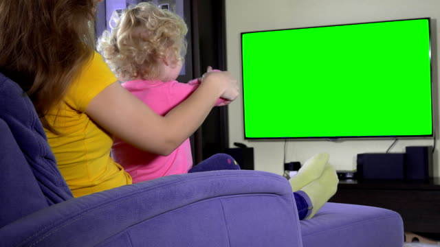 Young mother with her daughter girl relax on sofa and watch tv. Green screen video