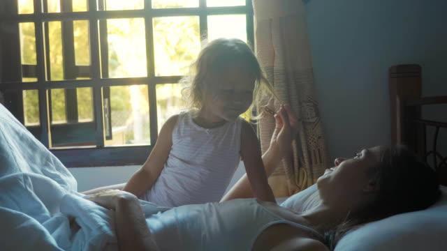 stockvideo's en b-roll-footage met jonge moeder met kleine schattige dochter in bed na wakker - alleenstaande moeder