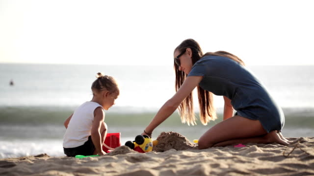 Young mother with little doughter playing with sand on the beach video