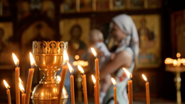 Young mother with little son in arms are near the icons in church video