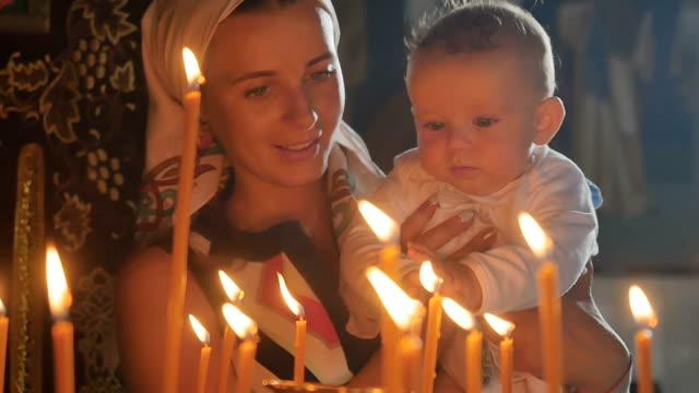 vidéos et rushes de jeune maman avec le petit garçon observe une bougies brûlant dans l'église - baptême