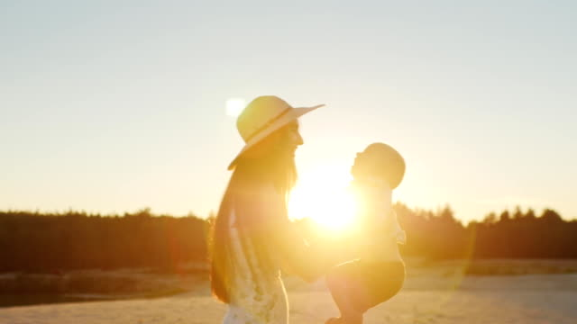 Young mother with long hair playing with his son at sunset, laughing together video