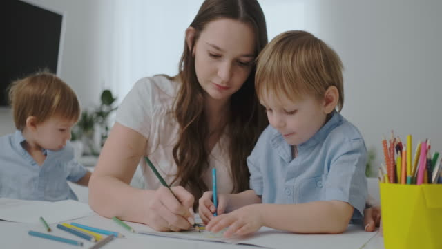 a young mother with two children sitting at a white table draws colored pencils on paper helping to do homework - matita colorata video stock e b–roll