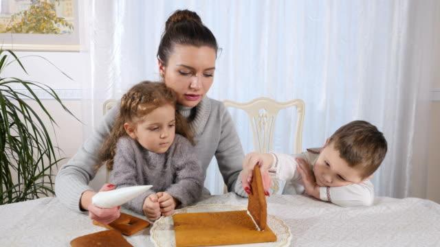 junge mutter mit zwei kindern verdienen ein lebkuchenhaus - lebkuchenhaus stock-videos und b-roll-filmmaterial
