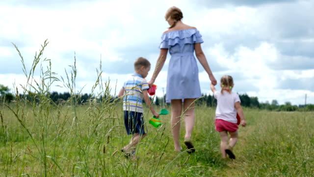 vídeos y material grabado en eventos de stock de joven madre con dos niños caminando en el campo de la hierba en verano. familia feliz en un paseo. - niñera