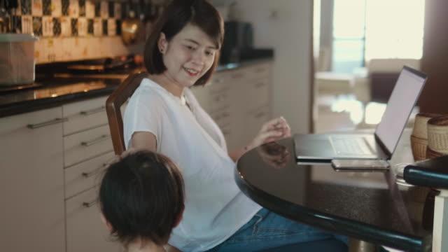 ung mamma arbetar på morgonen och son spelar. - working from home bildbanksvideor och videomaterial från bakom kulisserna