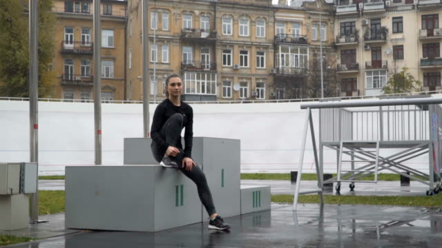 Young motivated woman at athletics podium in the stadium. 120fps video