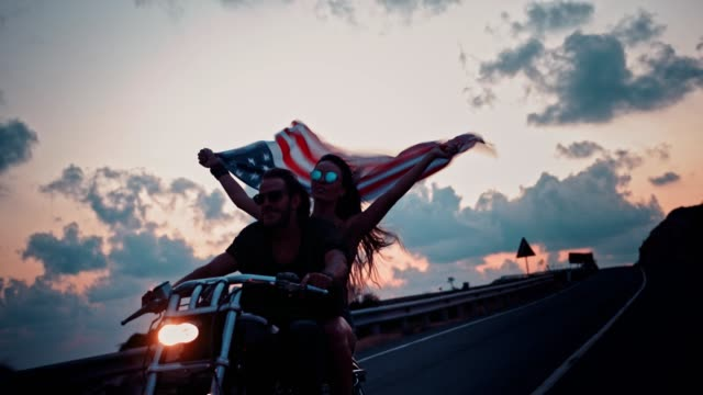 young motorcyclist couple riding on motorbike and waving american flag - giorno dell'indipendenza video stock e b–roll
