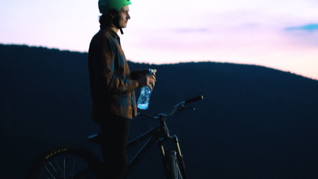 Young mountain bike cyclist drinking water at sunset. video