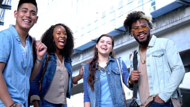 Young multi-ethnic adults hanging out in the city A group of four multi-ethnic young adults, two couples, hanging out together in the city. They are standing on a street corner, laughing and looking at the camera. physical position stock videos & royalty-free footage