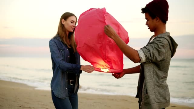 young multiethnic couple holding red paper lantern before launching. romantic date on the beach. attractive woman together with her african boyfriend holding lantern with fire before to let it fly - sky lantern stock videos and b-roll footage