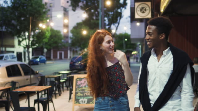 young multi-ethnic couple on the street at night - date night stock videos & royalty-free footage