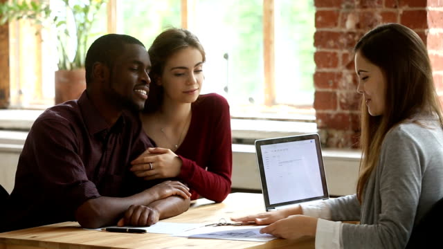 Young multi-ethnic couple planning mortgage meeting with real estate agent video
