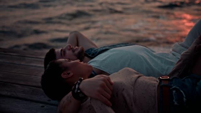 gün batımında iskelede yalancılık aşağı rahatlatıcı genç çok etnik gruptan oluşan çift - dalgakıran stok videoları ve detay görüntü çekimi