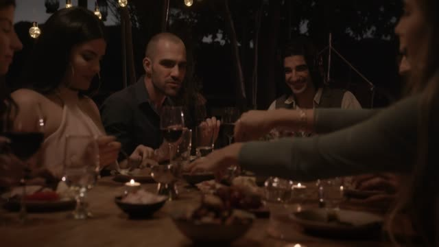 vidéos et rushes de jeunes amis multiethniques et couples célébrant lors d'un dîner élégant - diner entre amis