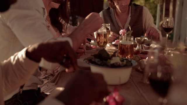 Young multi-ethnic friends and couples having mediterranean rustic feast