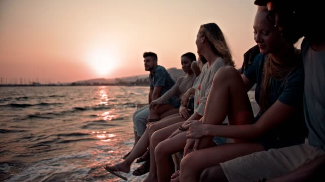 Young multi-ethnic friends and couples relaxing on jetty at sunset