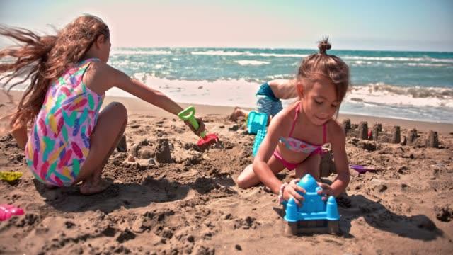 vídeos de stock e filmes b-roll de young multi-ethnic friends building sandcastles on beach in summer - torre estrutura construída