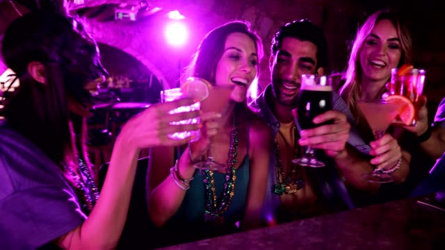 Young multi-ethnic friends celebrating Mardi Gras at New Orleans bar video