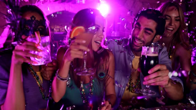Young multi-ethnic friends drinking and celebrating Mardi Gras at bar video