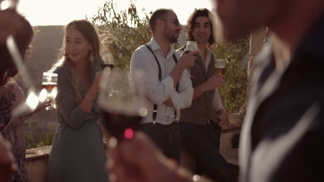 young multi-ethnic friends drinking wine and beer at rustic party - azienda vinivola video stock e b–roll