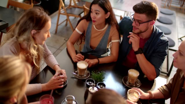 Young multi-ethnic friends having fun together at urban cofffee shop