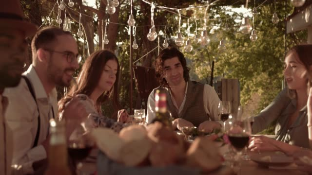 Young multi-ethnic friends having mediterranean lunch at village cottage video
