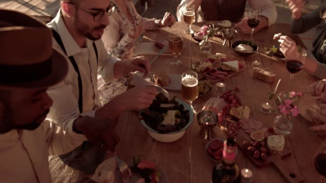 Young multi-ethnic friends having mediterranean meal at rustic restaurant video