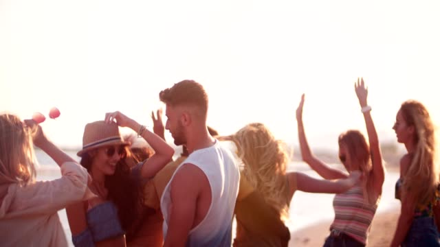 Young multi-ethnic friends partying and dancing at summer beach party