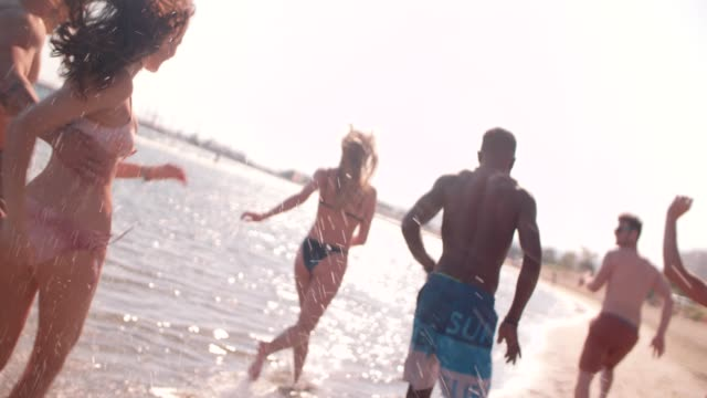 Young multi-ethnic friends running on the beach in summer