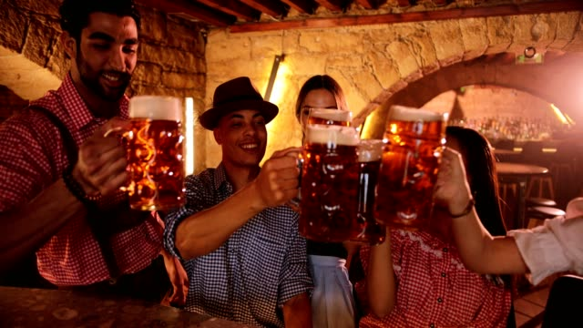 Young multi-ethnic friends with beer mugs and costumes celebrating Oktoberfest video