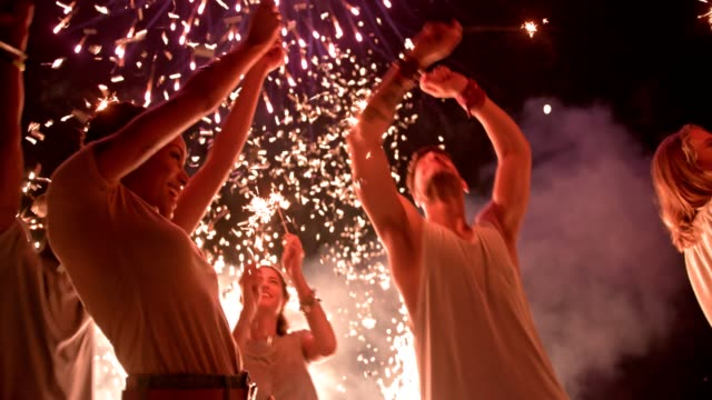 Young multi-ethnic hipster friends celebrating fourth of July with fireworks