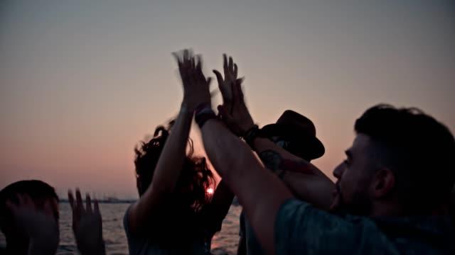 Amigos de jovem hippie multi-étnica dando toca aqui na praia - vídeo
