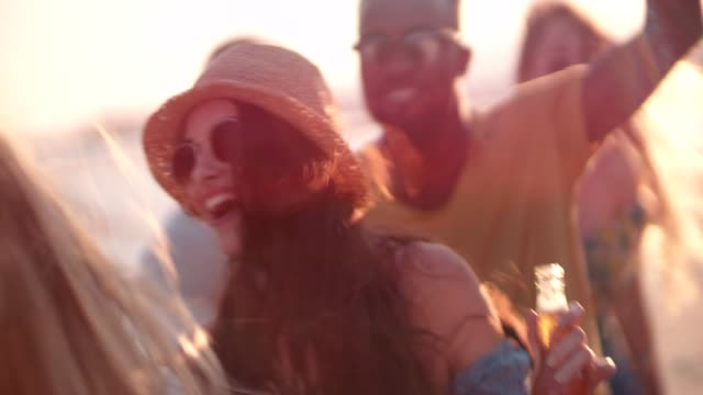 Young multi-ethnic hipsters dancing and drinking beer at beach party Young multi-ethnic hipster friends dancing, drinking beer and having fun at summer island beach party beach party stock videos & royalty-free footage