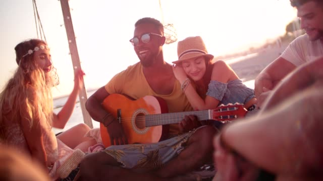 Young multi-ethnic hipsters listening to acoustic guitar at beach party